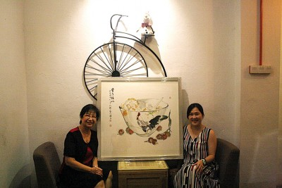 沈颖(右)的鸡公碗彩墨画,得到收藏家的赏识,左为槟水墨画协会会长翁丁健。