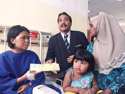 沙哈鲁丁(中)移交支票予司机遗孀米雅斯(左),由死者母亲峇斯达(右)及女儿陪同。
