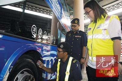 吉州陆路交通局执法人员检查长巴的轮胎花纹,右为陈佩红。