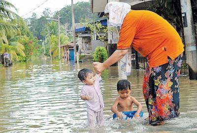 龙运县疏散中心灾民人数增加至933人,一名妇女带着两名孩子戏水,苦中作乐。