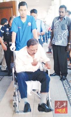 被告沙迪亚瑟拉坐在轮椅上被推出法庭,不断按着胸口脸部显得痛苦狰狞。
