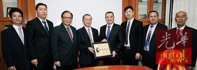 陈良成代表赠送纪念牌匾予受封拿督勋衔的陈德钦。