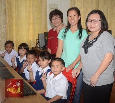 小凯逴(坐者右一)满心欢喜的上电脑课,站者右起级任老师许伟倩、母亲谢月凤及校长黄彩葳。