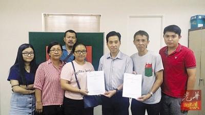 胡栋强(右三)移交文件予成功马来西亚华裔贩商基金(YPPKM)受惠者。