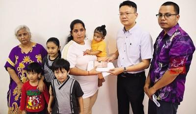 杨顺兴(右2)移交790令吉的援助金予索纳(右3),由垄尾区村长纳斯里(右起)、瓦拉及孩子们陪同见证。