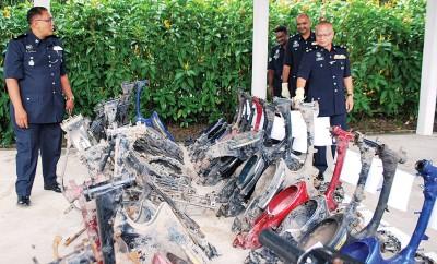 如吉菲利(左1)向阿都拉(右前1)汇报起回的摩托车残骸。