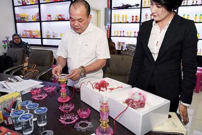倪来宝(左)向媒体展示盗版及正版莲花灯,右为曹慧玲。