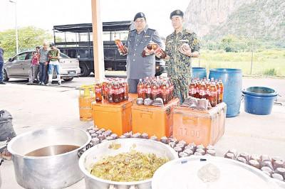 赛巴斯里(右)与执法员展示取缔的瓶装及包装哥冬水,以及提炼中的哥冬叶和水。