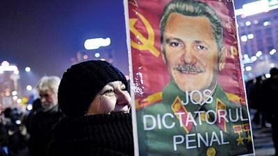 示威者持改造的德尔加瓦海报,要打倒独裁罪犯。(法新社照片)