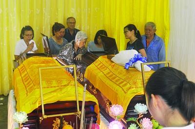 白秀爱(左3)以亲人陪同下瞻仰爱女吴美琴遗体后不禁落泪。