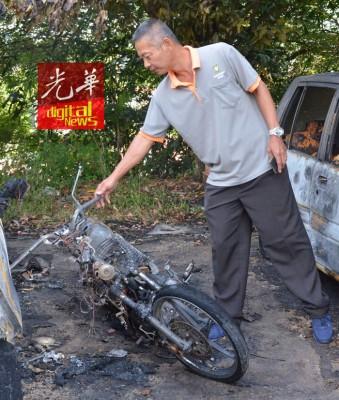 胡明彬向受害者了解事发情况,并查看被烧毁的摩托车。