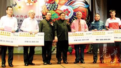 理事长庄佛和(中)及副理事长黄维忠(左3)主持颁发捐款给日新国中、独中及红新月会威中专区,代表接领义款者是林钿洝(左起)、陈奇杰、叶燕新、拿督陈睦来及陈顺德。