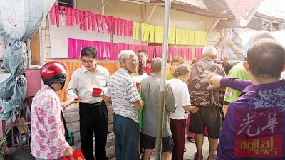 乐龄人士们井然有序地领红包,左2为黄泉安派赠红包。