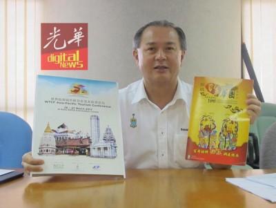 罗兴强展示亚太旅游论坛海报及百年华团特刊旧版本。