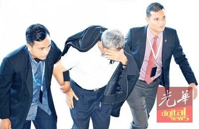 被告伊沙伊斯迈(中)被反贪会官员押上法庭时,低着头以手遮脸避开摄影镜头。