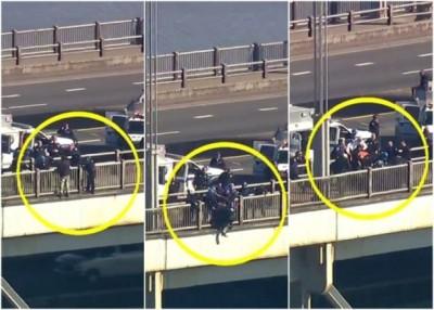 男子攀出大桥栏杆外企图轻生,多名警员趁机扑上前救人。