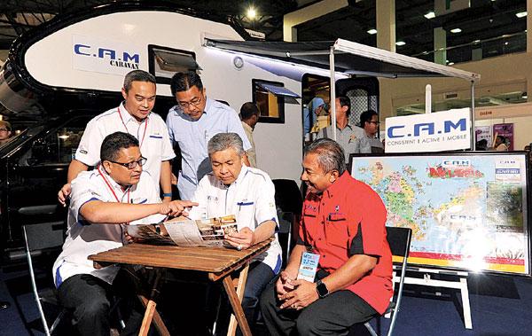 阿末扎希(中)巡视2017年马来西亚入境旅游展的展览厅。