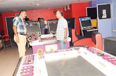 阿南杜莱(左)率领警员们突检娱乐中心的游戏机。