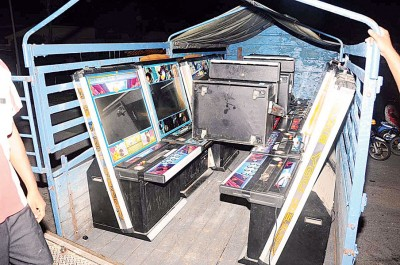 警方动用了数辆卡车把被扫荡的游戏机载往警局。