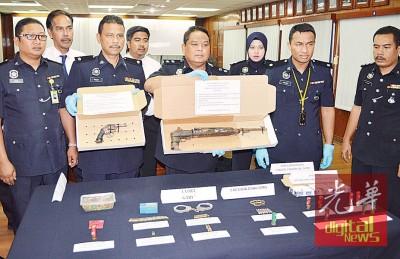 阿兹哈(右4)展示警方起获的两把枪支、子弹和武器。