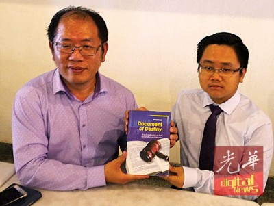黄伟益与王宇航出示《Document of Destiny》书籍,这可让大马人更了解我国宪法的书籍。