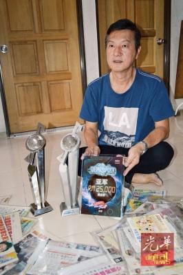 周振隆向媒体展示奕斌在本地赛事中获得亚军的奖座,欣慰孩子最后成功在国际赛夺冠。