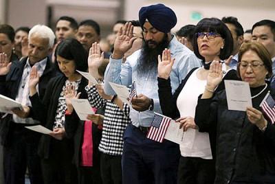在美国洛杉矶,一群移民在一项仪式上举手宣誓成为美国公民。