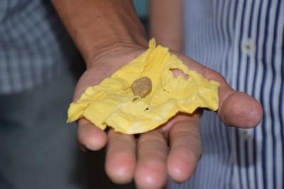 """""""辟邪石""""已机黄色小布块包裹,打开一看只不过是一颗普通的小石子。"""