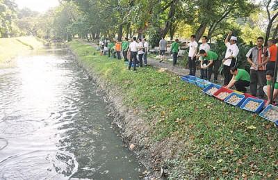 罗查里与履行社企责任,一起参与净化河流活动的2家公司员工,一起把泥球丢入诗布朗再也德哈卡河流。