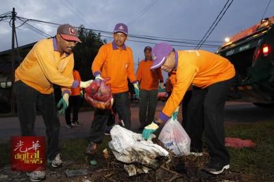 赞比里(右起)与占比利曼为体验清洁员工的劳苦,亲自动手收集垃圾。