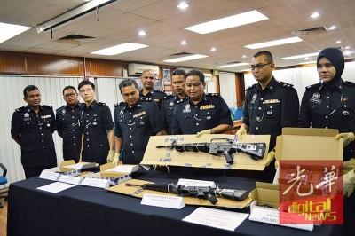 阿萨哈哈(右3)亮警方扣押查的莱福枪。