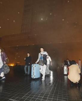 有房客拉着行李,提着大包小包逃命。