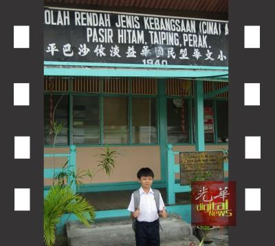 萧顺洋站在益华小学前拍照。