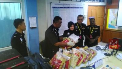 阿兹(左2)与查案官等人,在记者会出示毒品与行李袋。