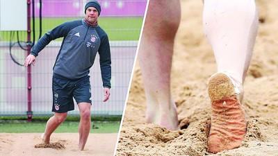 诺伊尔在小腿上贴着绷带,在沙地进行个人训练。