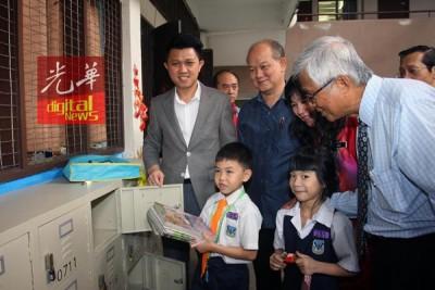 张盛闻(左)啊吉隆坡人民义华小推介储书柜,因减轻小学生的书包负担。