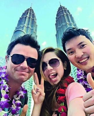2015年1月来马开唱时,邓紫棋与音乐监制Lupo(左)、商贩张丹乘空档到吉隆坡双峰塔游览。