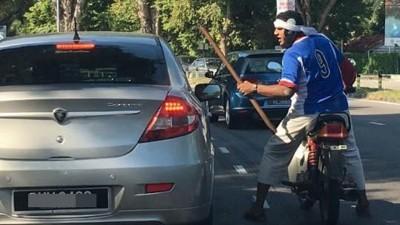 疯汉手持木棍骑摩托随机拦截轿车。