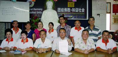 林荣坤(盖者右3)带领理事会宣布吉打佛学院执照得恢复。