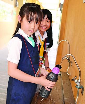 校方鼓励学生带着小水瓶到校,黄雯静和庄晶雯在装置食水。