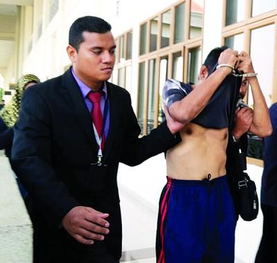 被告耶谷哈山被押离法庭时,盖上衣盖脸避开摄影镜头。