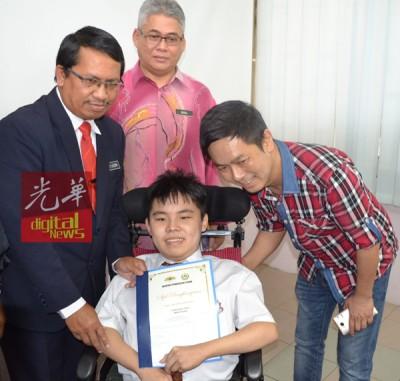 郑运万(右1)伴随坐着轮椅,生病上后天性肌肉萎缩症的男郑伟城打霹州教育局局长末拉欣手中接了优越奖状。