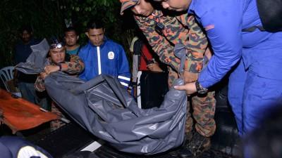搜救人员将其中一名死者阿米鲁哈奇米的遗体抬上车。