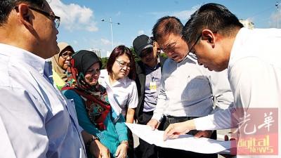 方津辉(右)向林峰成展示公司接下来的加宽道路计划。
