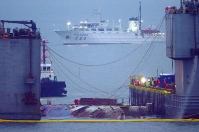 打捞团队在船体两端部署浮动式驳船,连拿66永钢索托住船体底部。(法新社照片)