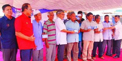 阿末巴沙移交援助金予班茶受惠渔民后合影。
