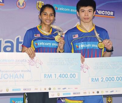 男单冠军梁峻豪(右)与女单冠军姬索娜(左)分享自己斩获的胜利品。