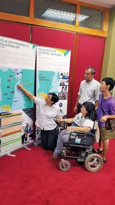 叶舒惠(左)及叶贤德(右2)向障友讲解交通大蓝图的展示资料。