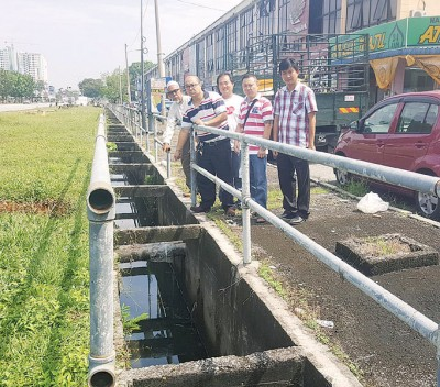 居民代表黄坤成、李国翰及市议员王泽钦等人视察排水沟内未移除的地下电缆。