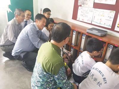 陈国平(左3)在出席汉民小学装置减轻学生书包橱柜记者会后,坦然应对记者询及丹斯里被查事件。